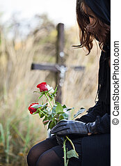 Widow at the cemetery holding red roses in her hands