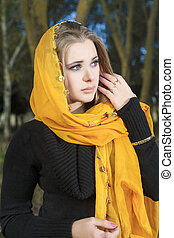 Grieving Woman in Kerchief Standing in Park. Vertical Image....