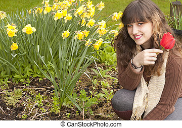 Gril loves daffodils - A teen girl sits in front of a bunch...