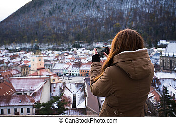 gril taking a photo of an old city