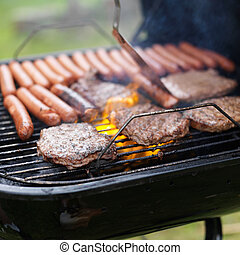 grill full of hotdogs and hamburger cooking