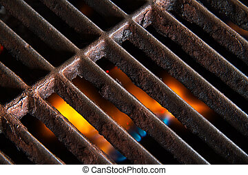 A crusty metallic grill grate with soft-focused flames beneath.