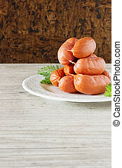 grill sausages on a plate on a wooden background. meat products.