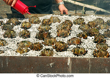 Grilled Artichokes - A man seasoned the grilled artichokes...