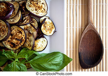 Platter of grilled aubergines with basil and wooden spoon on the side.