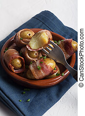 Grilled baby potato wrapped in bacon on the white background