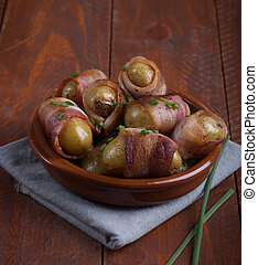 Grilled baby potato wrapped in bacon on the wooden background