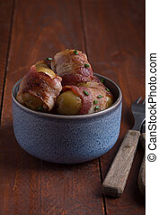 Grilled baby potato wrapped in bacon on the wooden table