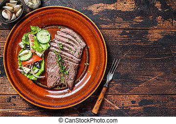 Grilled beef meat chop round steak on a plate with salad. Dark wooden background. Top view. Copy space