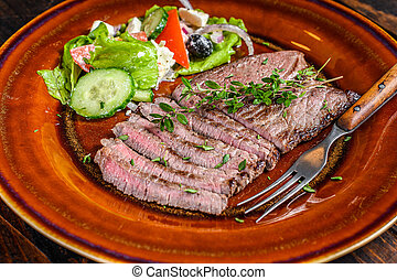 Grilled beef meat chop round steak on a plate with salad. Dark wooden background. Top view