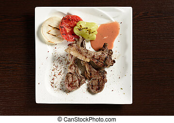 Grilled beef ribs with roasted vegetables, top view