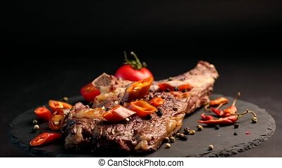 Grilled beef steak on bone with tomatoes and chili rotating...