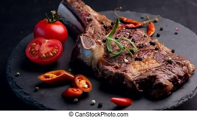 Grilled beef steak on bone with tomatoes - Close-up of...