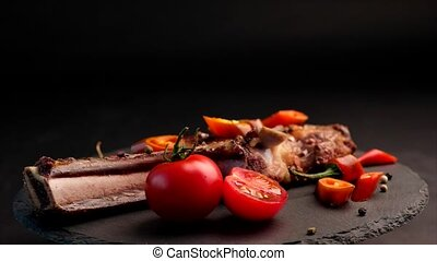 Grilled beef steak on bone with tomatoes rotating on the...