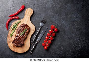 Grilled beef steak on cutting board over stone table. Top ...
