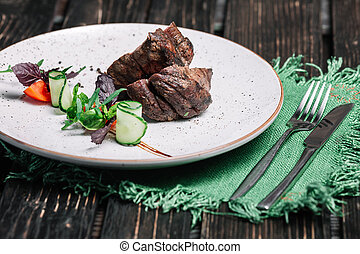 Grilled beef steak served with green napkin and cutlery on dark wooden background