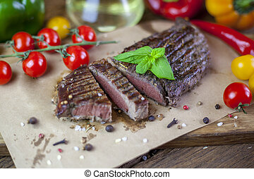 Grilled beef steak with french fries from beef on dark wooden background