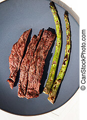 Grilled beef steak with Green asparagus on blue plate and white background top view, barbecue dry aged steak