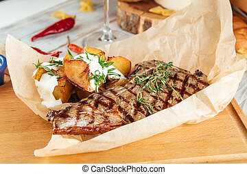 Grilled beef steak with potatoes on wooden board