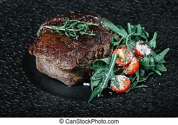 Grilled beef steak with salad on dark background