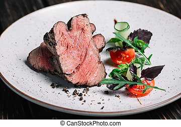 Grilled beef steak with salad on dark wooden background
