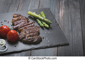 Grilled beef steak with vegetables on a black background