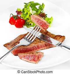 Grilled beef steak with vegetables on white plate