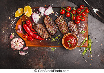 Grilled beef steaks with spices on wooden cutting board, dark background