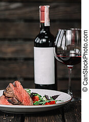 Grilled beefsteak with bottle and glass of red wine on dark wooden background