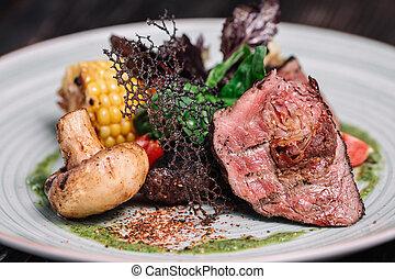 Grilled beefsteak with vegetable on dark wooden background