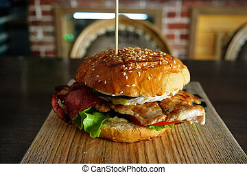 Grilled Burger with backon and salad served on cutting board with blurred pub interior on background