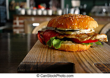 Burger with fyed egg and backon served on cutting board with blurred pub interior on background