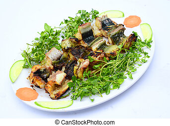 Grilled catfish with cucumber, carrot and herbs on white platter