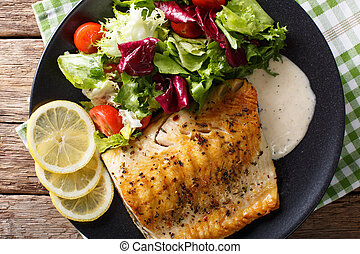 Grilled char fillet with mixed salad and sauce on a plate ...