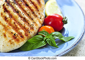 Grilled chicken breasts on a plate with fresh vegetables