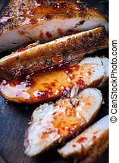 Grilled chicken fillets on wooden cutting board with sauce