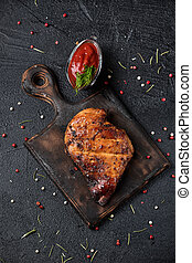 Grilled chicken fillets on wooden cutting board with tomato sauce.