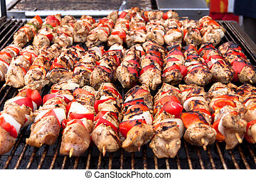 Grilled chicken kebabs - Rows of grilled chicken kebabs at...