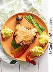 Grilled chicken leg with potatoes above view
