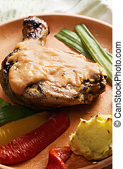 Grilled chicken leg with potatoes closeup