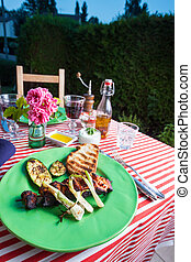 grilled chicken meat outdoor on a green plate