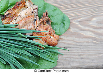 grilled chicken with fresh vegetables on wooden background