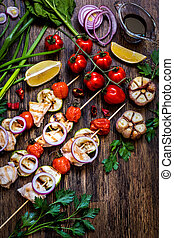 grilled chicken with zucchini, tomatoes, onions and herbs on wooden background