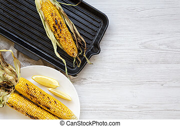 Grilled corn cobs with lemon, top view. Copy space.