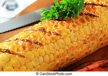 Grilled corn and fried pieces of salt pork