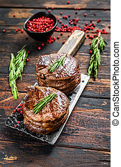 Grilled fillet mignon steak on a meat cleaver. Dark wooden background. Top view
