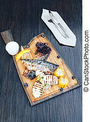 Grilled fish on a wooden cutting board with vegetables. wooden background