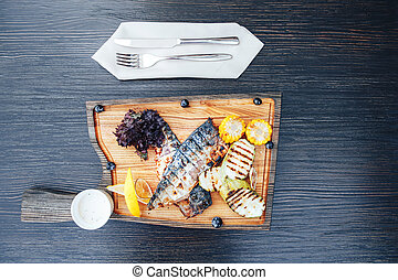 Grilled fish on a wooden cutting board with vegetables. wooden background. top view