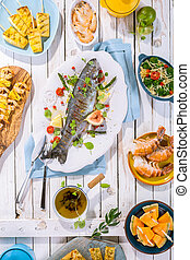 Grilled Fish on Table with Other Dishes