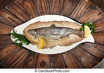 Grilled fish on white plate with herbs and lemon on wooden background, top view